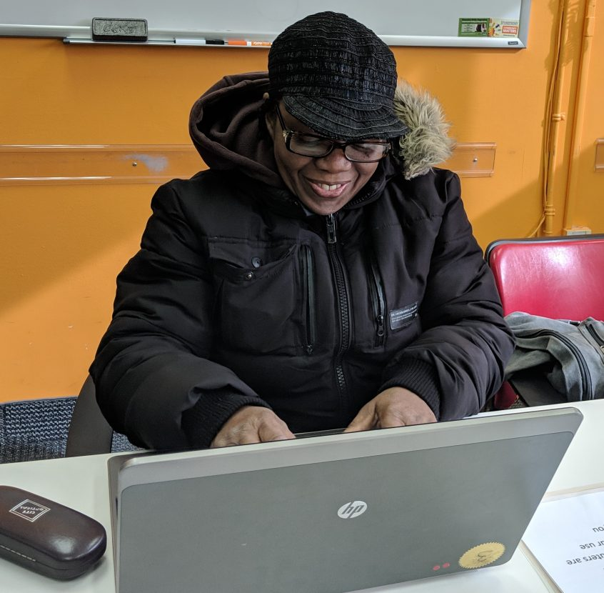 Photo of a smiling woman using a laptop computer at Job Search Club.